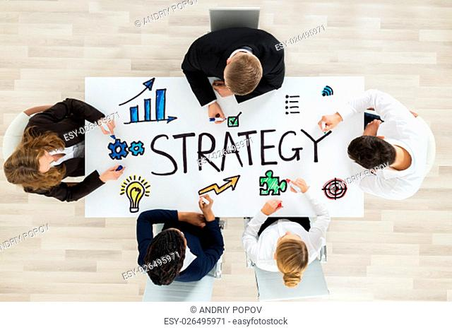 Team Of Professional Businesspeople Drawing Strategy Diagram With Marker