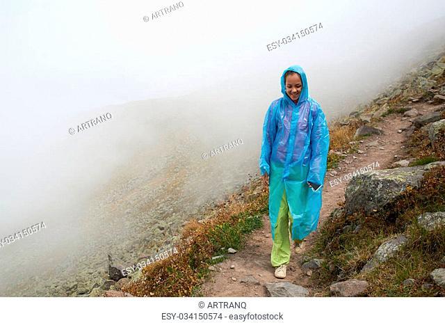 The girl in the blue raicoat ia walking in the canyon