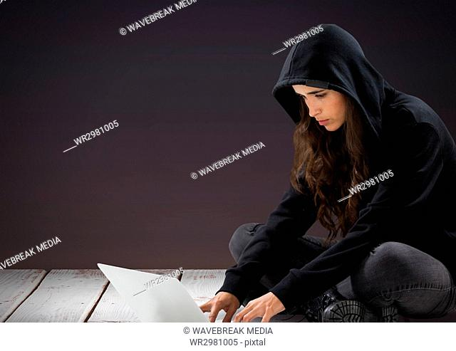 3d Woman hacker using a laptop in front of purple background