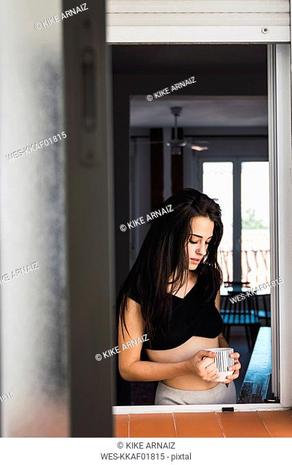 Serious beautiful young woman with cup of coffee at the window at home