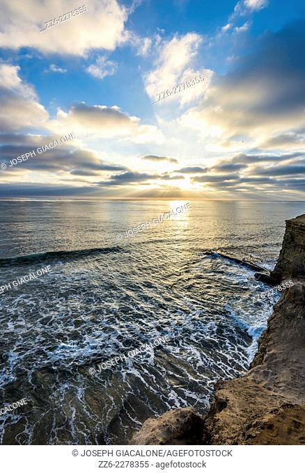 Majestic sunset over the Pacific Ocean producing sunbeams through the clouds. Sunset Cliffs Natural Park, San Diego, California, United States