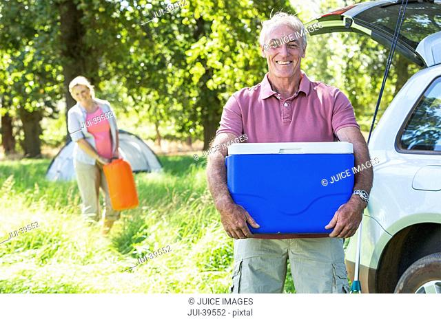 Senior Couple Unpacking Car For Camping Trip In Countryside
