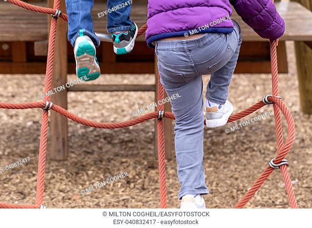 Young children playing on a climbing frame at Battersea Park, London