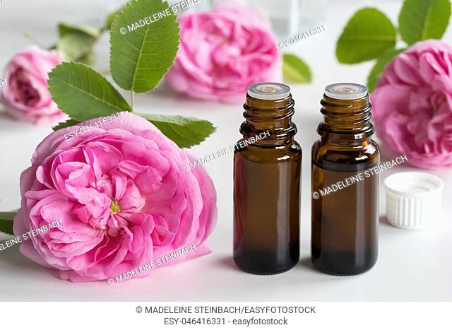 Two bottles of rose essential oil with rose flowers on a white background