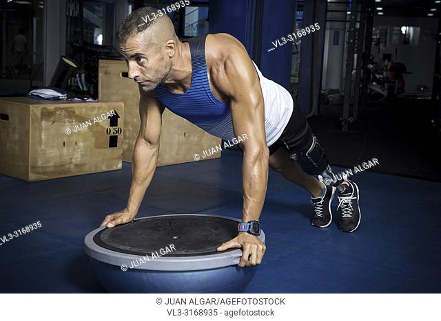 Confident muscular sportsman with artificial leg limb training with bosu ball in gym doing push-ups