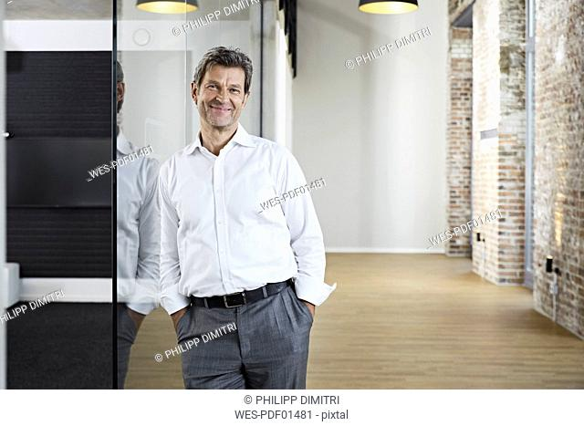 Portrait of smiling businessman leaning against glass pane in modern office