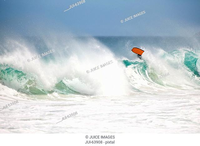 Body boarder riding wave