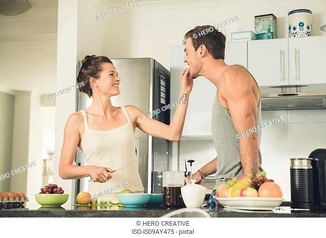 Young woman feeding fruit to boyfriend at kitchen counter
