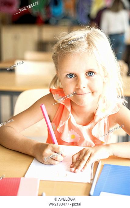 Portrait of cute girl drawing during art class