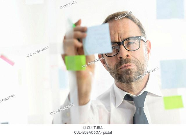 Businessman sticking adhesive notes to glass wall