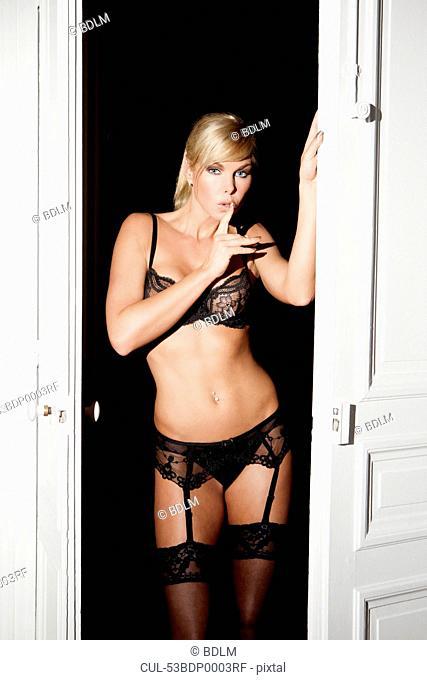 Woman in lingerie standing in doorway
