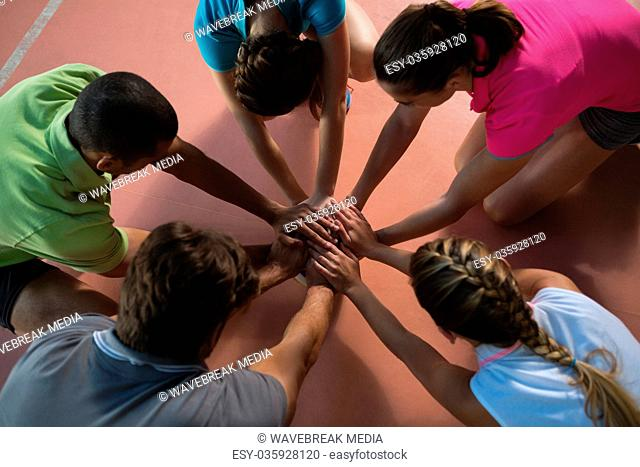 High angle view of volleyball players stacking hands