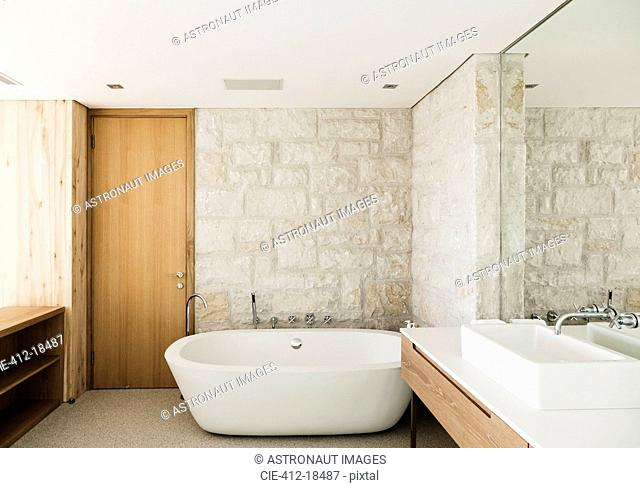 Stone walls behind soaking tub in modern bathroom
