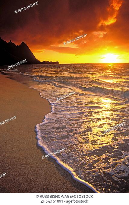 Sunset over surf, sand and peaks from Tunnels Beach, Ha'ena, Island of Kauai, Hawaii USA