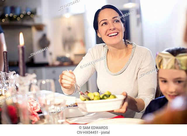 Smiling woman serving Brussels sprouts at Christmas dinner table