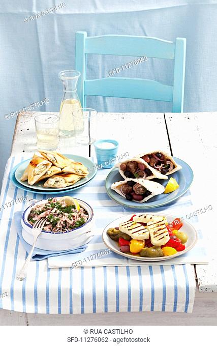 Various Greek appetisers: grilled haloumi with peppers, keftedes with pita bread and tzatziki, marinated octopus, feta cheese pasties