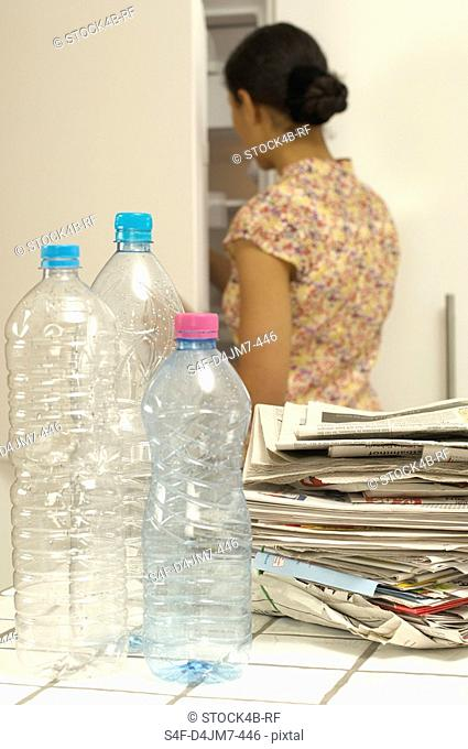 Woman in kitchen with plastic bottles and old newspapers