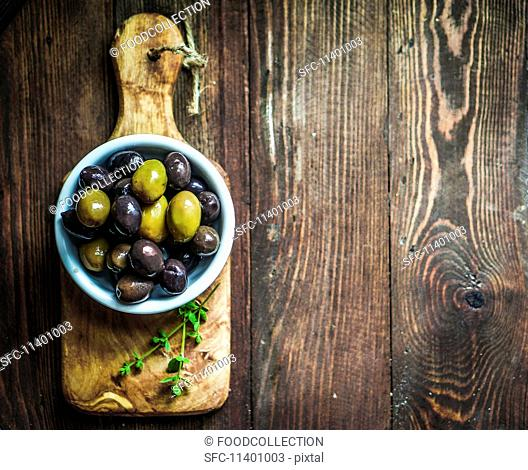 Green and black olives in a dish on a chopping board (seen from above)