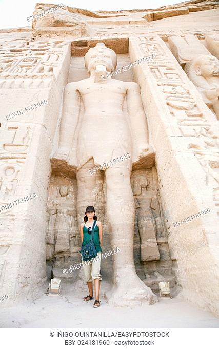 tourist woman standing down giant Ramses sculpture in facade of famous Egyptian temple of Nefertari and Hathor, in Abu Simbel