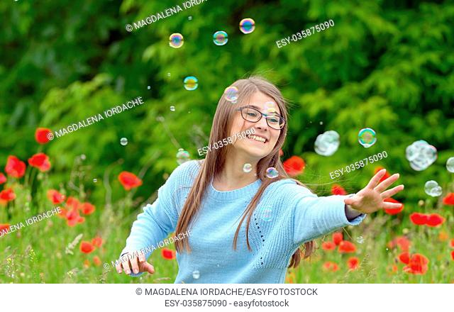 Girl Catching Soap Bubbles on spring field