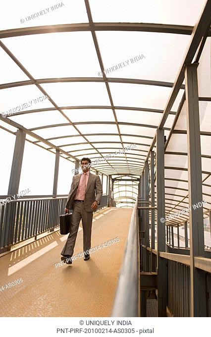 Businessman walking on a footbridge, Gurgaon, Haryana, India