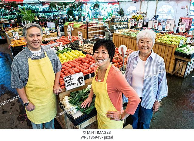 High angle view of man and two women wearing aprons standing at stall with fresh tomatoes at a fruit and vegetable market