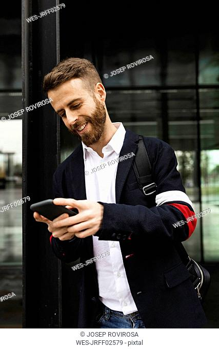 Smiling stylish businessman using cell phone in the city