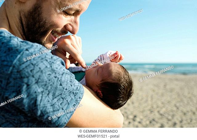 Father with his newborn baby girl on the beach