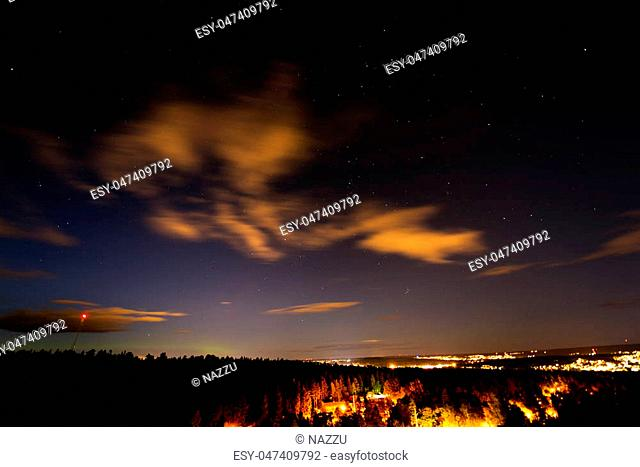 The landscape with a shining city and a forest under the sky with stars. Sweden