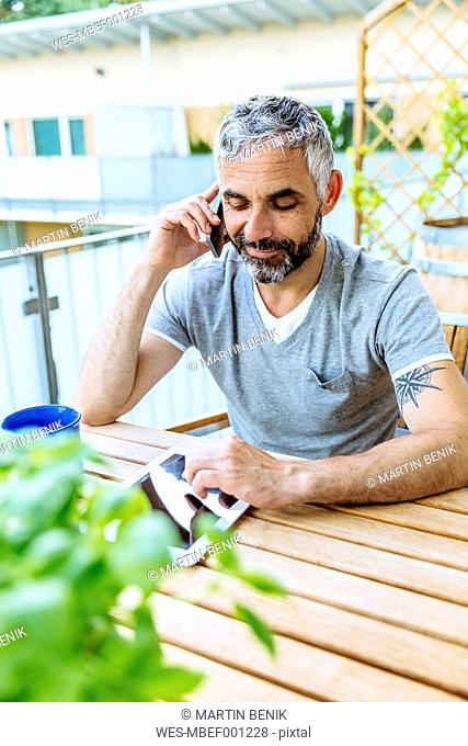 Portrait of man sitting on his balcony telephoning with his smartphone while using digital tablet