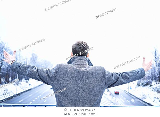 Back view of man with arms outstretched standing on bridge above motorway