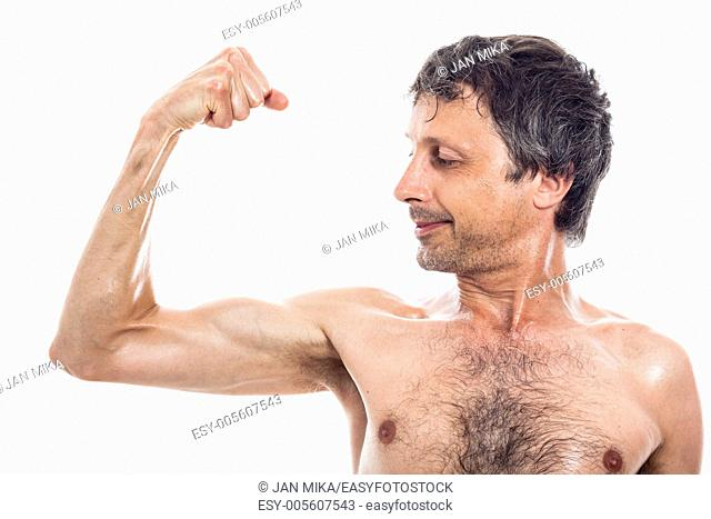 Slim shirtless man looking at his biceps, isolated on white background