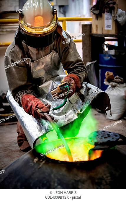 Male foundry worker taking temperature of furnace in bronze foundry