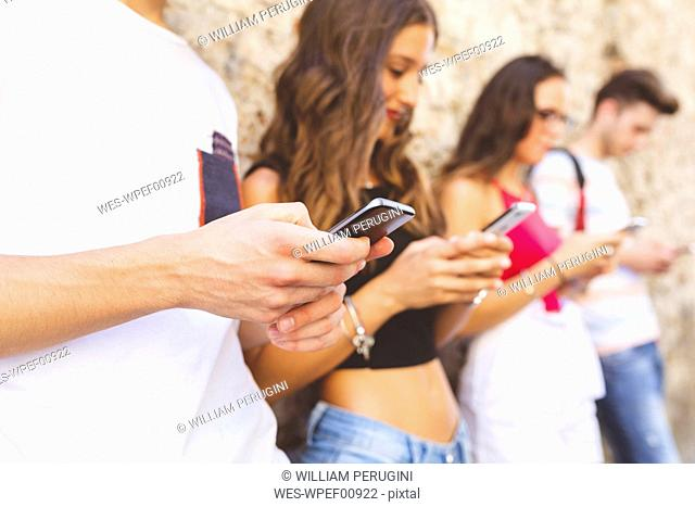 Close-up of group of friends standing at a wall using their cell phones