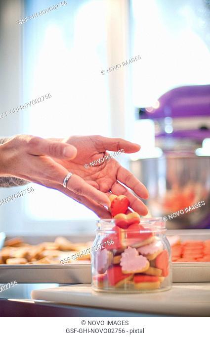 Woman Putting Cookies in Jar