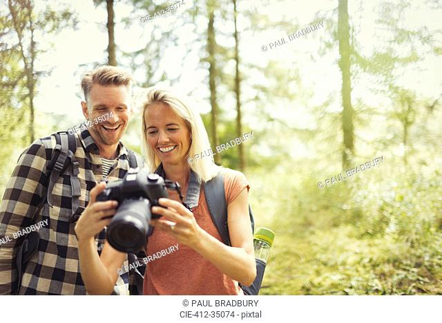 Smiling couple hiking, viewing digital SLR camera in woods