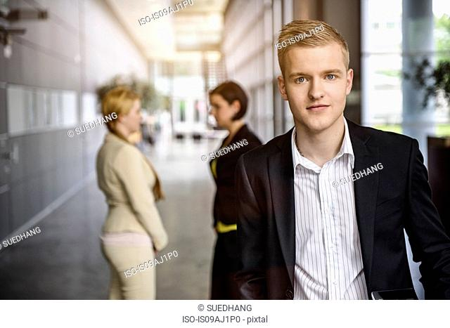 Portrait of ambitious young businessman in office corridor
