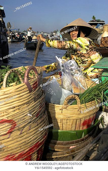 Woman in conical hat with baskets of vegetables padddles boat Cai Ran floating market near Can Tho Vietnam