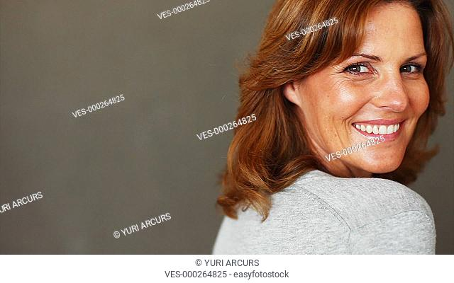 Cute mature woman smiles at you with copyspace next to her