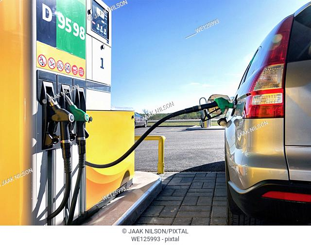Car in gas station. Closeup of fueling, petrol dispenser and handles. Back side view of car with tail lights. Estonia