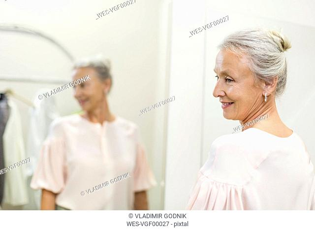 Smiling senior woman in a boutique reflected in mirror