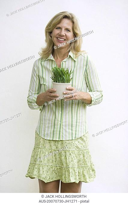 Portrait of a mature woman holding a potted plant and smiling