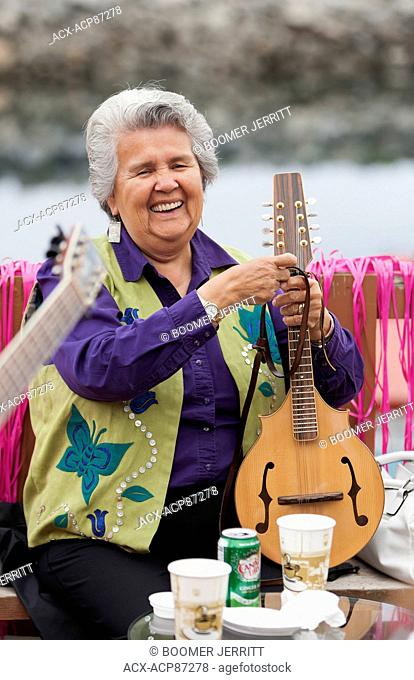 A smiling elder first nations senior adjusts her mandolin during a musical gathering of first nations friends on the deck of a restaurant in Alert Bay
