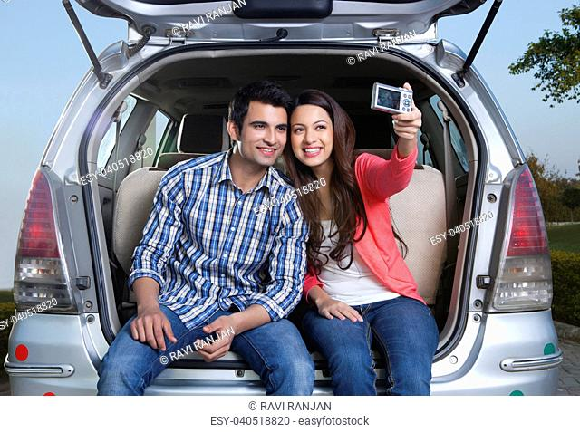 Young man and young woman sitting in the trunk of a car