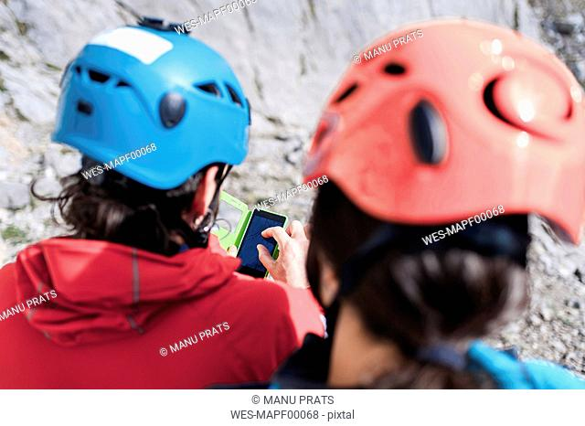 Spain, Picos de Europa, climbers wearing helmets using cell phone
