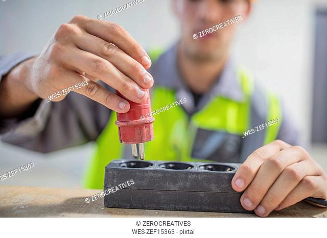 Close-up of electrician putting plug into power strip
