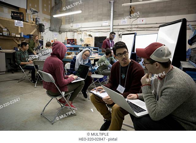 Team of hackers brainstorming using laptop at hackathon in workshop