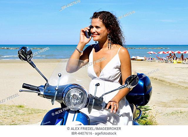 Woman in white dress and decorative earrings with cell phone on Vespa Primavera scooter on the beach, Senigallia, Adriatic Coast, Marche, Italy
