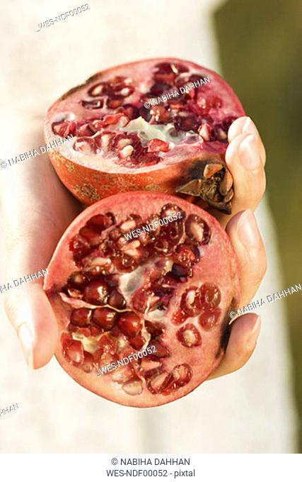 Woman holding pomegranate half's, close-up