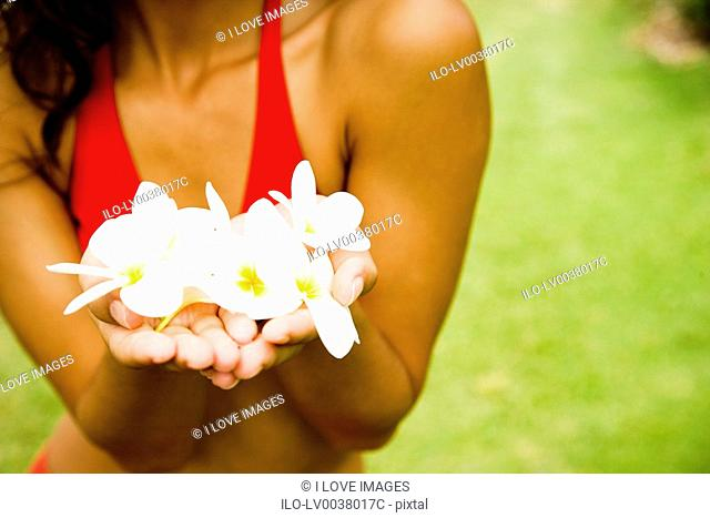 Woman in a tropical setting holding frangipani